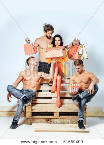 Pretty girl or ?ute woman with handsome men muscular young people or friends with muscle torso hold presents in boxes and bags on wooden bench on white background