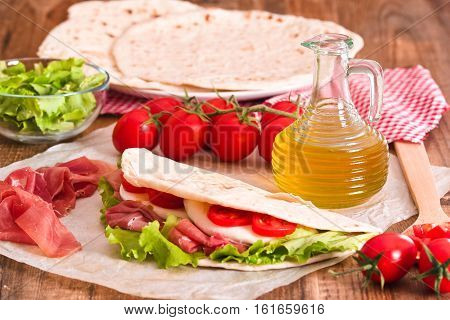 Piadina with ham and lettuce on baking paper.