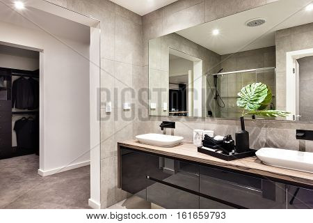 Modern bathroom closeup to a mirror and countertop sink and towels next to liquid soap dressing room can be seen through the door
