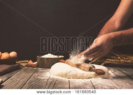 Men hands sprinkle a dough with flour close up. Man preparing bread dough