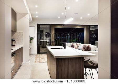 Modern kitchen countertop closeup with a view of patio area from the outside at night