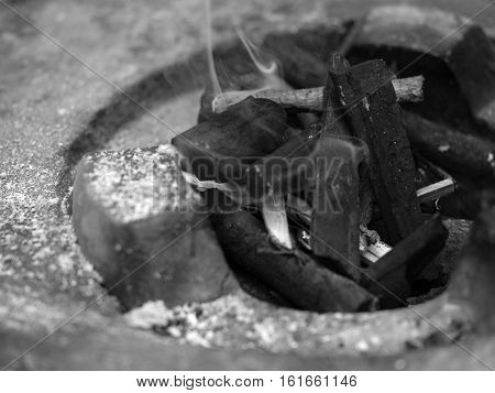BLACK AND WHITE PHOTO OF CHARCOAL FIRE IN STOVE