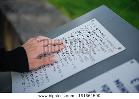 text for the blind on metal plate in park.