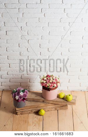 beautiful rose flowers bouquet in boxes pink and violet colors near green apples on wooden planks on wood floor on white brick wall background copy space