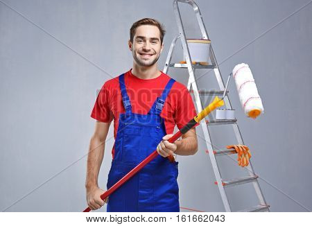 Handsome worker with paint roller in empty room