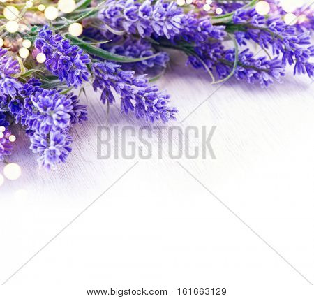 Lavender flowers over white wooden table. Aroma lavender flowers border design. Aroma treatment concept