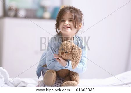 Funny little girl sitting on bed with cuddly toy