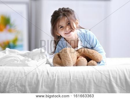 Funny little girl lying on bed with cuddly toy poster