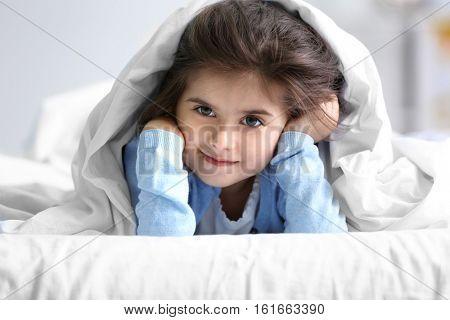 Cute little girl lying on bed under blanket