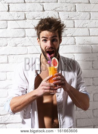 young surprised bearded sexy macho man with stylish beard in unbuttoned white shirt and muscular bare torso on athletic body holding glass of alcoholic orange cocktail on white brick wall background