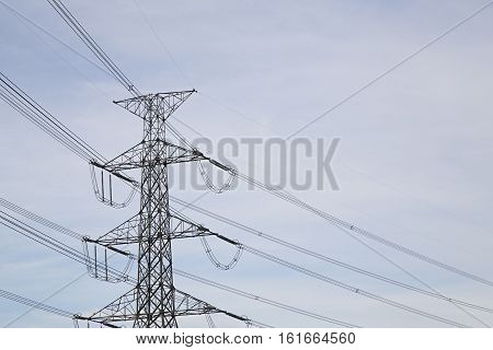 View side of high voltage poles in blue sky