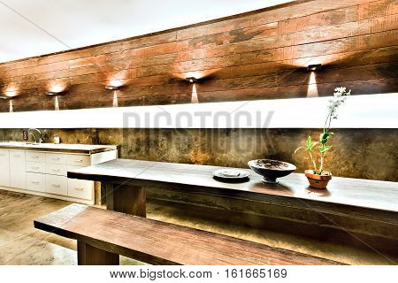 Outdoor dining or patio area with wooden furniture including benches and tables under the flashing lights