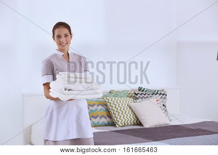 Female chambermaid  holding clean white folded towels in bedroom