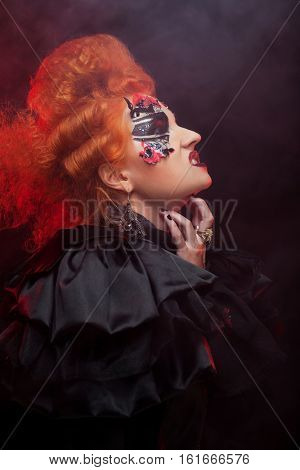 Gothic redhair witch. Dark woman. Artistic make up. Halloween picture.