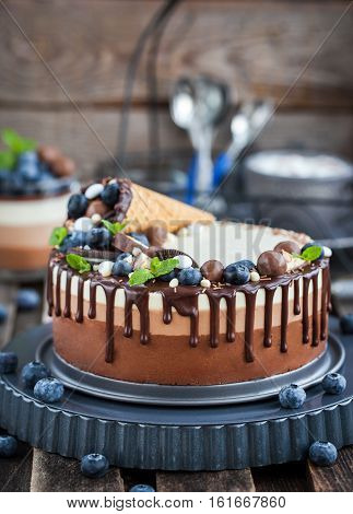 Three Chocolate Mousse Cake Decorated With Waffle Cone, Fresh Blueberry, Mint, Candies And Frosting