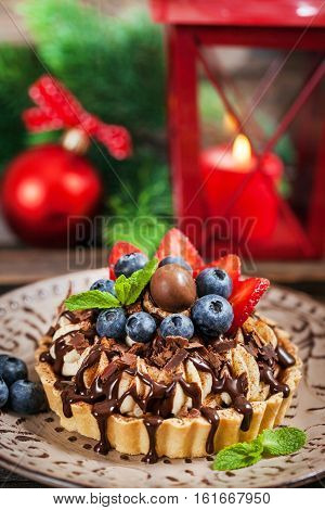 Banoffee chocolate pie decorated with chocolate fresh blueberry and strawberry holiday christmas background