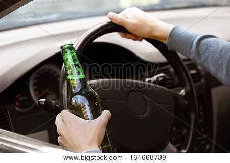 Man holding bottle of beer while driving car, closeup. Don't drink and drive concept