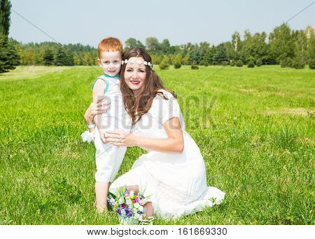 Happy family. Young mother and kid boy on sunny day. Portrait mom and son on nature. Positive human emotions feelings joy.
