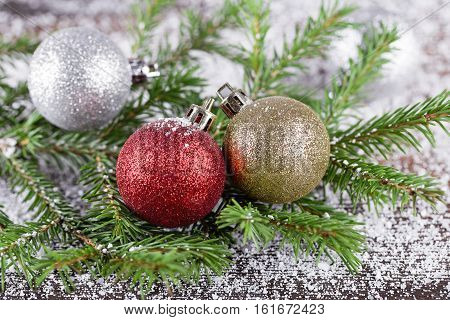 Three decoration balls on fir-tree branch with snow. New Year card design.