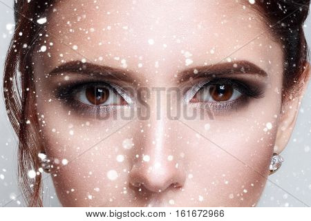 winter christmas people beauty concept- close-up of beautiful womanish eye fashion . half-face cropped pictures over snow background
