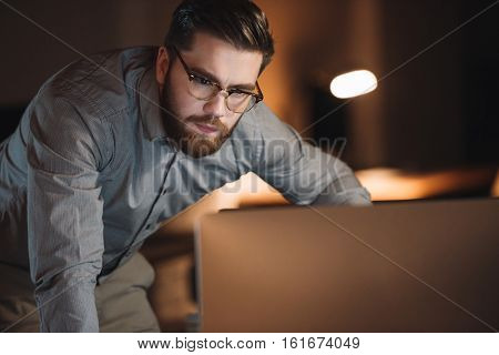 Image of concentrated designer dressed in shirt and wearing eyeglasses working late at night.