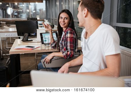 Side view of coworkers sit by the tables in office and look eyes to eyes.