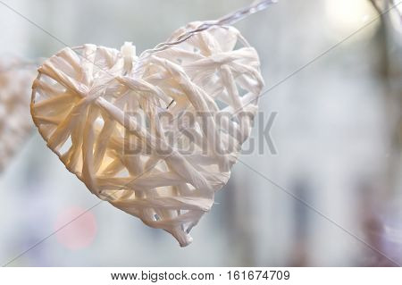 Closeup image of a white paper heart with small light inside.