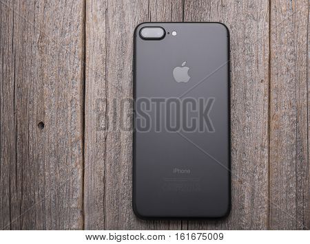 UZHGOROD, UKRAINE - DECEMBER 15, 2016: New black iPhone 7 Plus from the company Apple on a woden background, back view, studio photo, on December 15, 2016 in Uzhgorod, Ukraine.