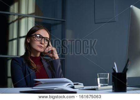 Portrait of committed female boss in formal clothes and glasses working at desk in dark office late at night