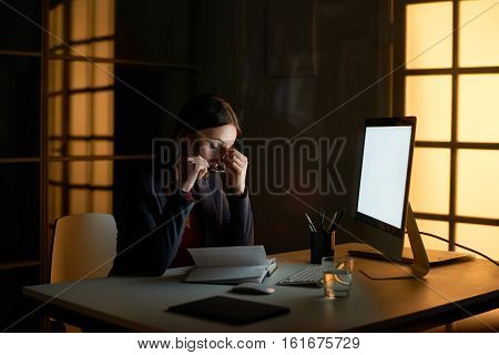 Portrait of exhausted brunette woman wearing formal suit sitting at computer desk with eyes closed and rubbing her nose bridge trying to relax and relieve headache in dark office late in evening.