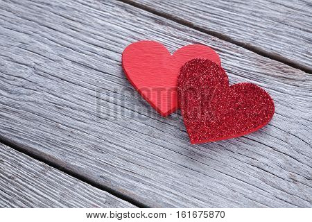 Valentine background with handmade glitter hearts on rustic wood. Happy lovers day card mockup, copy space