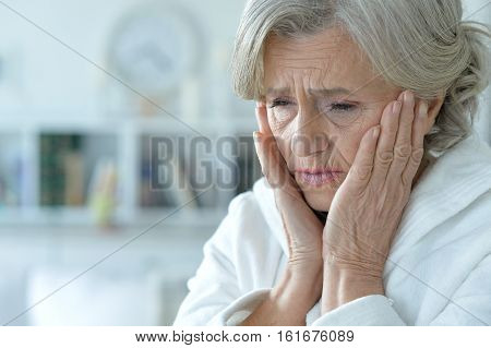 Portrait of sad senior woman with hands on her cheeks