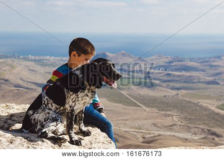 boy rest on the rocks over the valley and little surprised