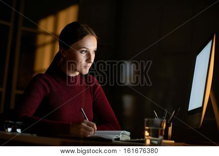 Young smart-looking brunette woman making notes writing down from bright computer screen while working at desk in dark room late in evening