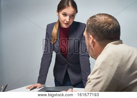 Serious daunting woman wearing formal suit leaning at desk with mature man sitting at it, talking down to him in empty gray room