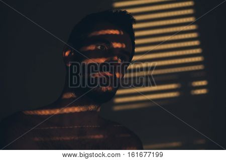 Young man sad and depressed sitting alone behind the sunblinds