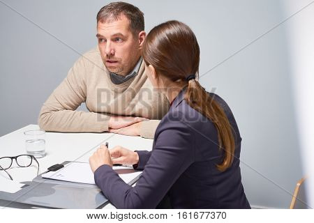 Confused  mature man talking to female official sitting at desk in empty gray interrogation room
