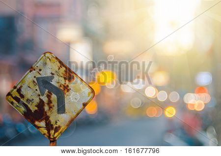 Old Curve Road Warning Sign On Blur Traffic Road With Colorful Bokeh Light Abstract Background.