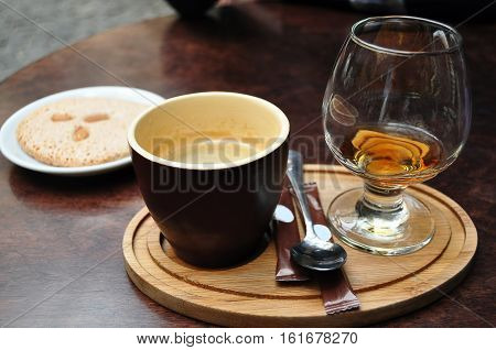 Dark Ceramic Cup Of Coffee, Glass Of Cognac And Italian Almond Cantuccini Cookie On A White Plate On