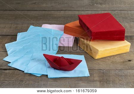 Paper napkins and paper boat on a wooden table