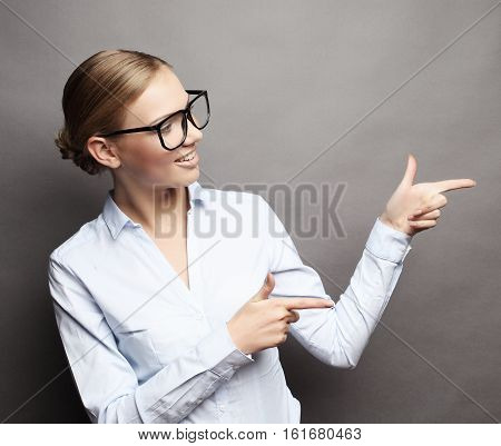 Happy smiling young beautiful business woman showing something or copyspase for product or sign text,  over grey background