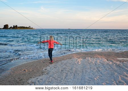 a happy young girl is dancing on the beach