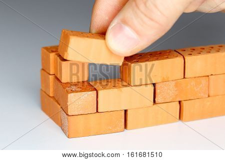 a hand is laying a brick to a wall