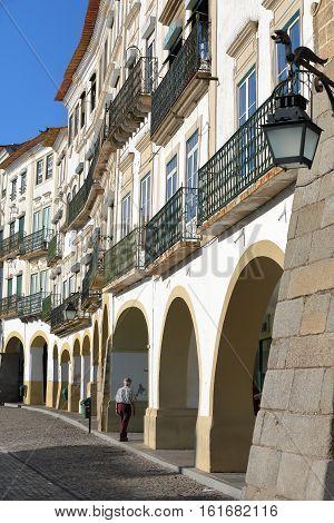 EVORA, PORTUGAL - OCTOBER 8, 2016: Typical house facades and arcades at Giraldo Square