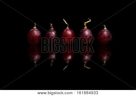 Five rred grapes isolated on black reflective background