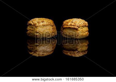 Two small cornbread isolated on black reflective background