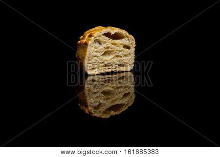 Half of a small corn bread isolated on black reflective background