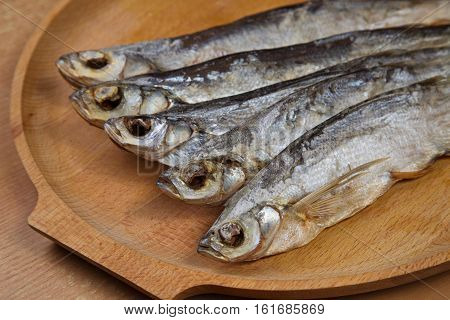 Dried fish on a wooden tray. Stockfish.