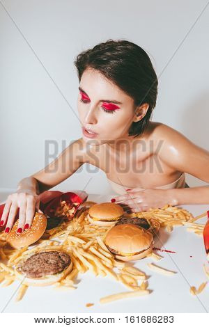 Attractive young woman with bright makeup eating fast food over white background