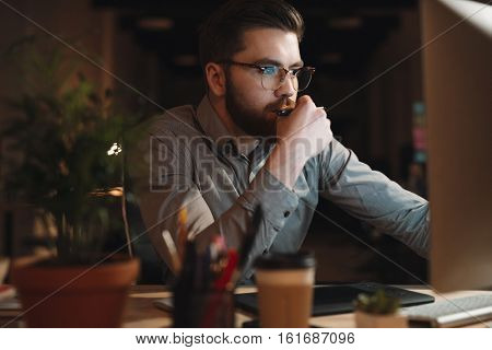 Young web designer dressed in shirt and wearing eyeglasses working late at night and looking at computer. Holding pen.
